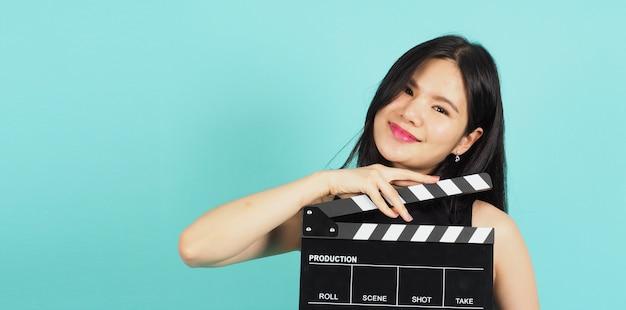 Tablica klapy lub klapa filmu w nastoletniej dziewczynie lub kobiecie ręcznie. używa w produkcji wideo, filmie, przemyśle filmowym na zielonym lub tiffany blue background.she nosi czarną sukienkę