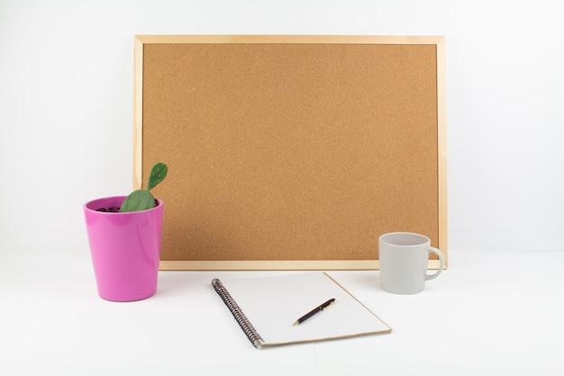 Tablica korkowa na notatki z długopisem i notatnikiem w biurze
