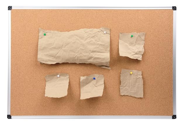 Tablica korkowa z aluminiową ramą i dołączone kawałki brązowego papieru, deska na białym tle