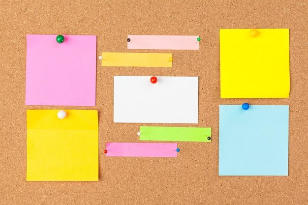 Tablica korkowa z kilkoma kolorowymi pustymi notatkami z pinami