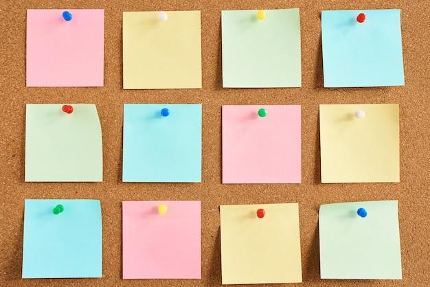 Tablica korkowa z przypiętymi kolorowymi pustymi notatkami