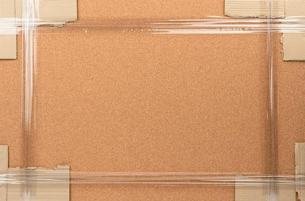 Tablica korkowa zapakowana w taśmę klejącą, pełna rama