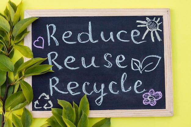 Tablica kreda reduse reuse recycle znak na żółtym tle z zielonymi liśćmi. widok z góry.