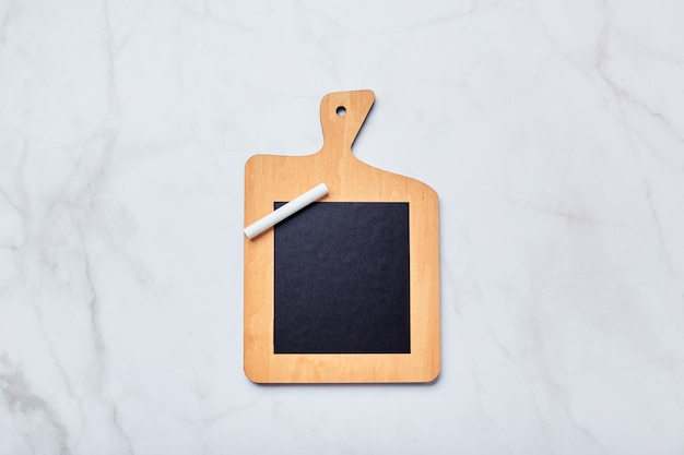 Tablica kredowa w formie kuchennej deski do krojenia z kawałkiem kredy na jasnym marmurowym stole. tablica do pisania notatek, list, przepisów