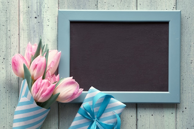 Tablica kredowa z różowymi tulipanami i zapakowanymi pudełkami prezentowymi. leżał płasko z przestrzenią tekstową