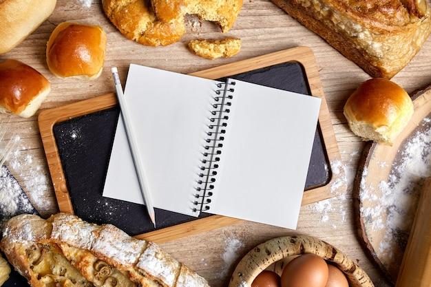 Tablica łupkowa z pieczywem dookoła i książką kucharską