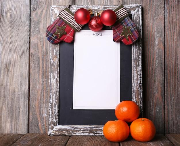 Tablica menu z dekoracją świąteczną na tle drewnianych desek