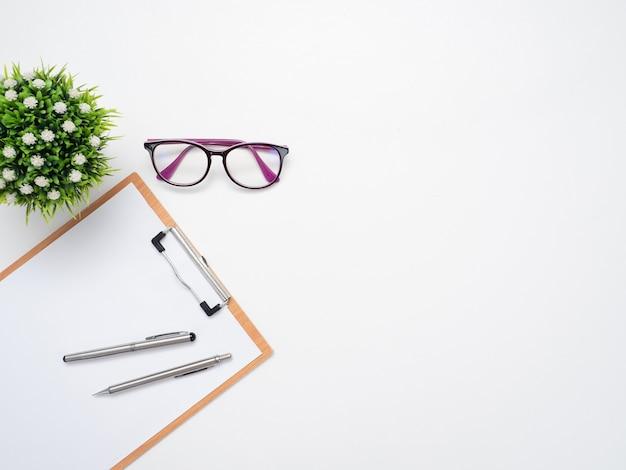 Tablica na dokumenty z długopisem i okularami z wazonem na stole z widokiem na miejsce na kopię