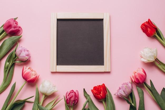 Tablica na różowym tle z tulipanów.