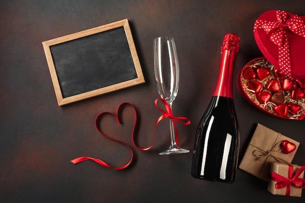 Tablica na walentynki z kieliszkami szampana i wstążką w kształcie serca.