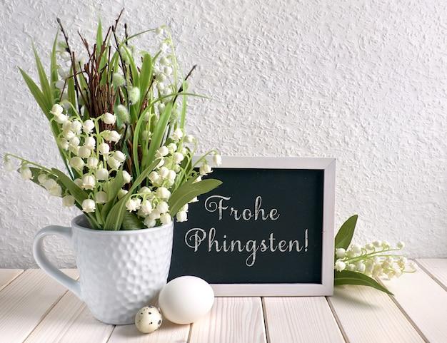 """Tablica ozdobiona kwiatami konwalii i jajkami, tekst w języku niemieckim oznacza """"happy pentacost"""""""