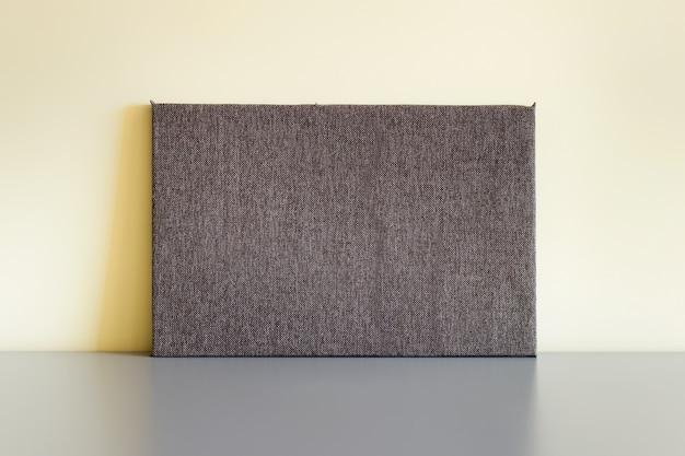 Tablica prostokątna pokryta brązową tkaniną w kratę stojąca na szarej powierzchni odbijającej światło obok żółtej ściany.