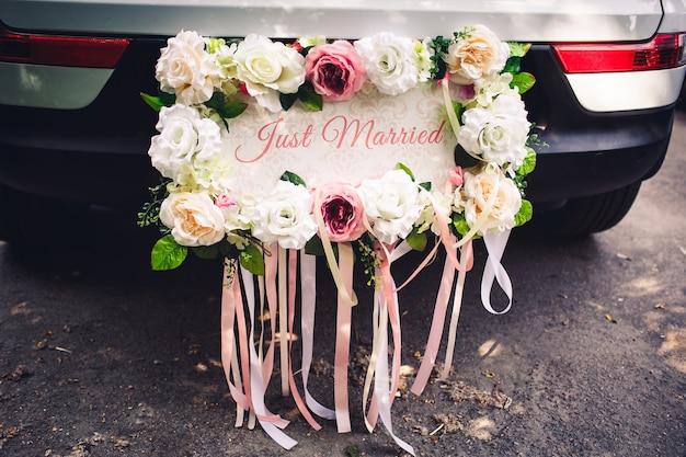 """Tablica ślubna """"just married"""" na samochód ozdobiona jest kwiatami."""