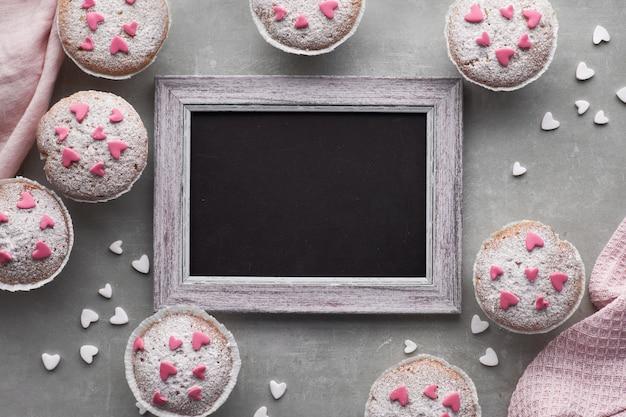 Tablica w ramce z posypanymi cukrem babeczkami z różowymi i białymi polewami z kremówki