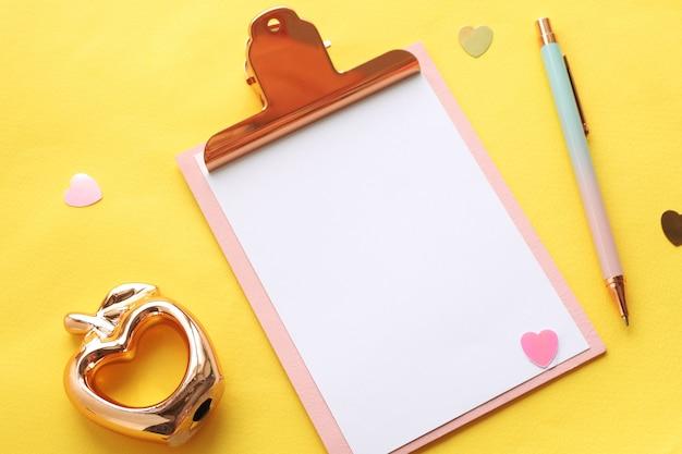 Tablica z klipsem z białym prześcieradłem, figurka złotego jabłka z dziurą w sercu, różowo-niebieski długopis, serduszka na jasnożółtym tle.