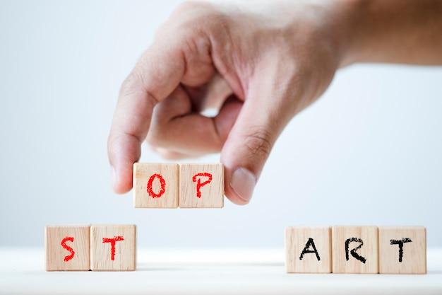 Tablica z ludzką ręką rozpocznij i zatrzymaj słowo kluczowe na drewnianej sześciennej