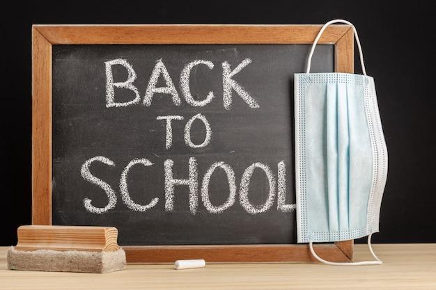 Tablica z napisanym tekstem z powrotem do szkoły i maska na twarz wisząca na tablicy