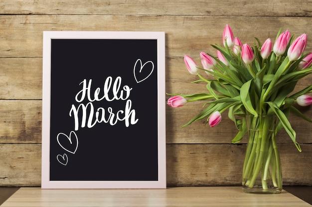 Tablica z napisem hello march, wazon z tulipanami na drewnianej powierzchni. koncepcja początku wiosny.