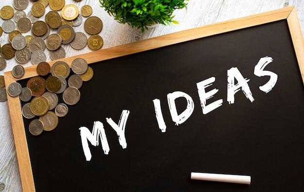 Tablica z napisem moje pomysły i metalowe monety na szarym drewnianym stole. koncepcja finansowa.