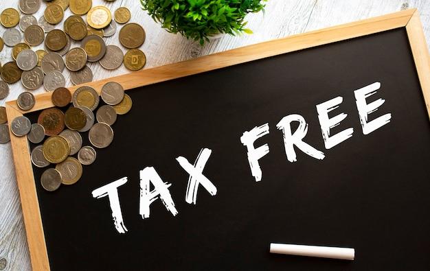 Tablica z napisem tax free i metalowymi monetami na szarym drewnianym stole.