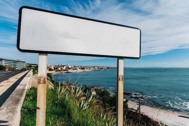 Tablica z nazwami geograficznymi / billboard z białą kopią miejsca na napis na brzegu oceanu