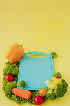 Tablica ze świeżych warzyw na żółtym tle. pojęcie zdrowego odżywiania