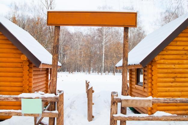 Tablica znak i nowy żółty drewniany dom w zimowym lesie