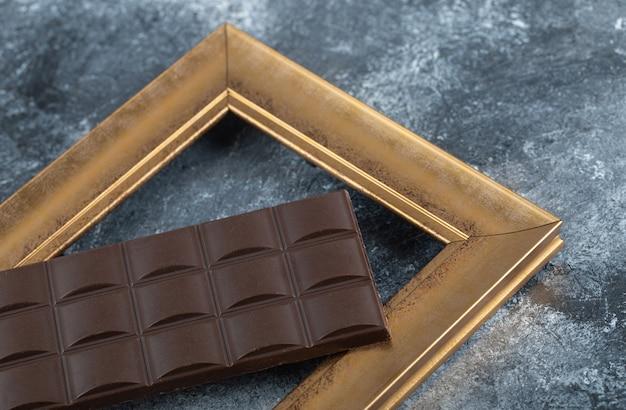 Tabliczka ciemnej czekolady w ramce.