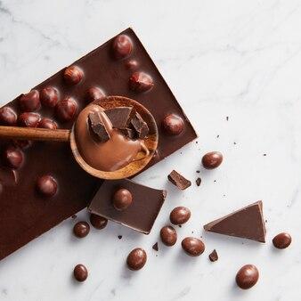 Tabliczka czekolady i karmelu z drewnianą łyżką na białym tle
