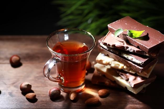 Tabliczka mlecznej czekolady. domowa mleczna czekolada z migdałami i suszonymi truskawkami. kawałki mlecznej czekolady. czekolada mleczna bez etykiety. zestaw czekolady z herbatą.