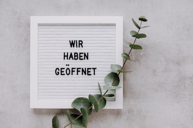 Tabliczka na drzwi wir haben geoeffnet oznaczająca po niemiecku we are open biała tablica z eukaliptusem