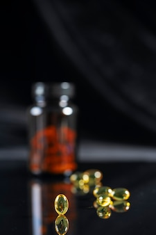 Tabliczki leżą na lustrzanym czarnym tle, odbijają się w nim. ciemna butelka z lekami nieostrymi.