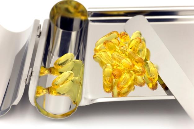 Taca do liczenia tabletek z żółtą miękką kapsułką żelatynową.