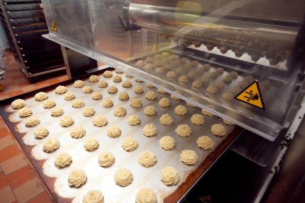 Taca gotowych ciasteczek jest pobierana z przenośnika taśmowego w piekarni