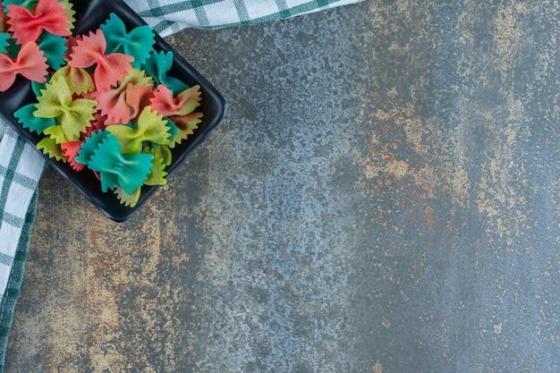 Taca kolorowych makaronów farfalle na ręczniku, na marmurowym tle.