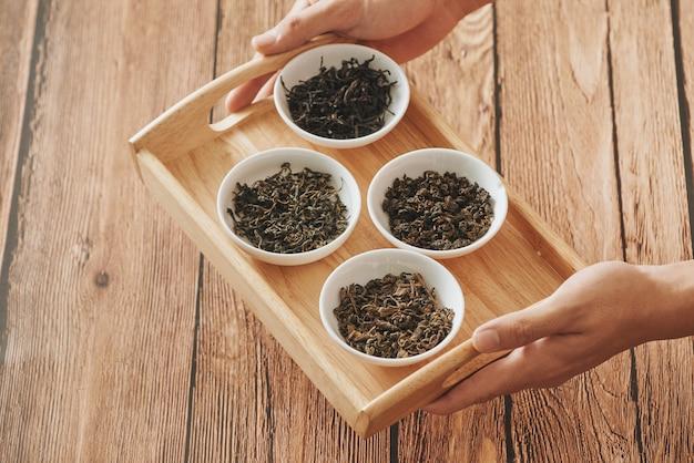 Taca na rękach z białymi miseczkami suchych liści herbaty