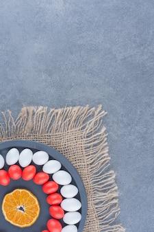 Taca pełna dziąseł i liści na trójnogu na marmurowym tle.