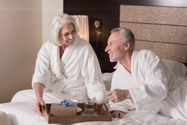Taca śniadaniowa. zachwycona, uśmiechnięta starsza kobieta siedząca na łóżku i trzymająca tacę śniadaniową podczas śniadania z mężem i wyrażająca radość