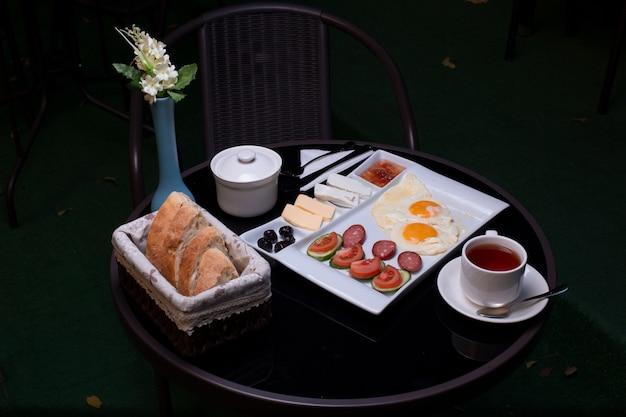Taca śniadaniowa ze smażonymi jajkami, kiełbasami, serem, dżemem, masłem, chlebem i filiżanką herbaty.