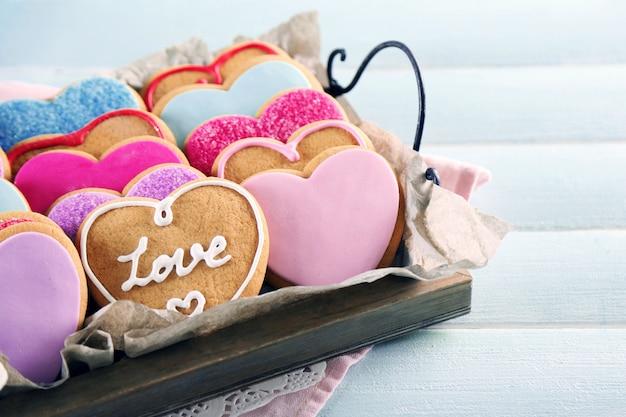 Taca z ciasteczkami miłości na niebieskim tle drewnianego stołu