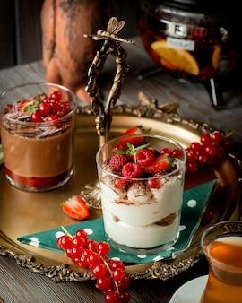 Taca z dwiema szklankami tiramisu i budyniem czekoladowym przyozdobionym jagodami _