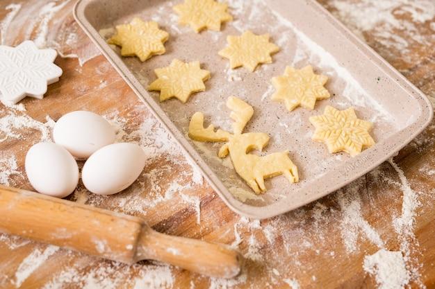 Taca z dwoma rzędami surowych świątecznych ciasteczek z trzema jajkami, wałkiem do ciasta, mąką i krajalnicami w pobliżu na stole