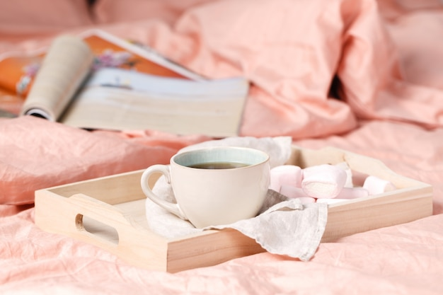 Taca z filiżanką gorącej herbaty, listem miłosnym i czasopismami w łóżku