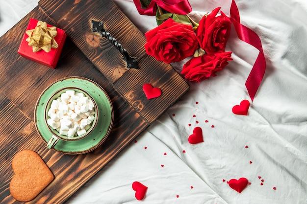 Taca z filiżanką kawy na łóżku i kwiatach, koncepcja romantycznego śniadania