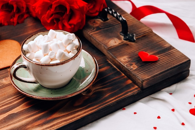 Taca z filiżanką na łóżku i kwiatami, romantyczne śniadanie