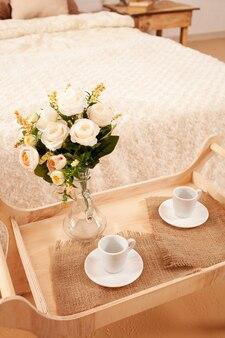 Taca z filiżankami i kwiatami w wazonie.