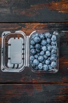 Taca z jagodami, na starym ciemnym tle drewnianego stołu, widok z góry płaski lay