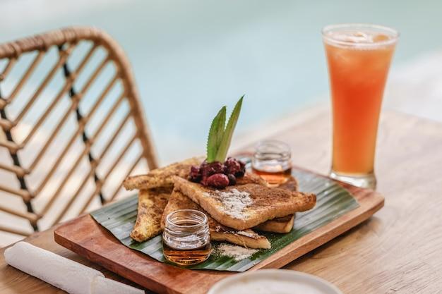 Taca z jedzeniem i ciasteczkami na drewnianym stole obok szklanki soku i kawy