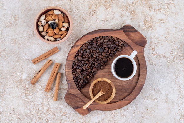 Taca z kawą obok lasek cynamonu i małej miseczki z różnymi orzechami