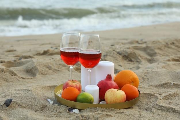 Taca z lampkami wina, owocami i świecami na piaszczystej plaży